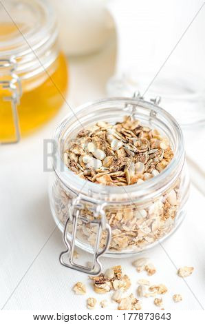 Good morning with homemade granola cereal, nuts, honey for breakfast on white background. Healthy food, Diet, Detox, Clean Eating or Vegetarian concept.