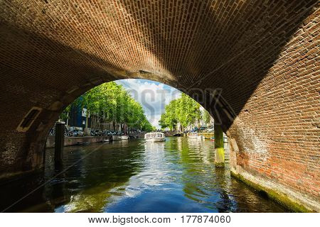 Spring sunny Amsterdam. The bright clear blue sky with white clouds. Boat trip on the canals of Amsterdam. The bridge over the water. Travel to Europe. Canals in dutch