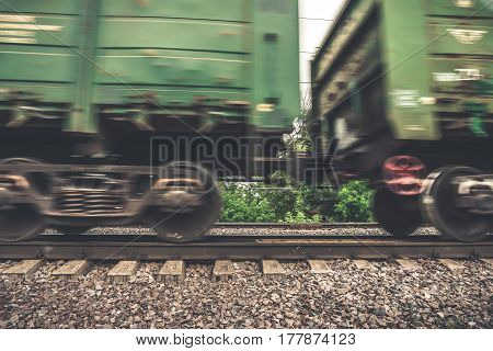 Freight train, wheels, side view, railway wagons with motion blur effect. Transportation, railroad, toned image
