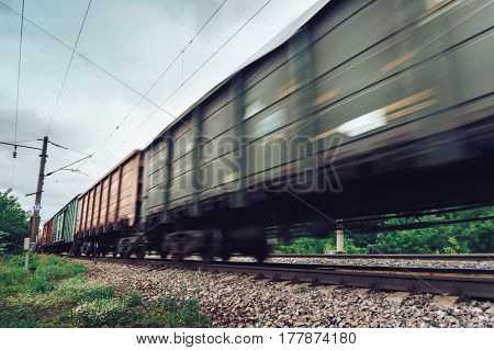 Freight train, railway wagons with motion blur effect, perspective. Transportation, railroad, toned image