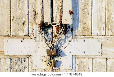 old vintage wooden door with chain and padlock on the wall