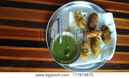indian potato fritters with green chutneyin steel plate