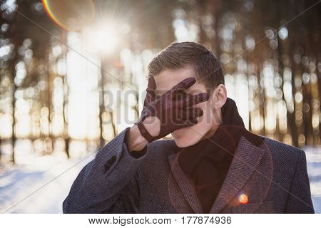 Concept idea in nature. Young attractive man with short hair wearing a gray winter coat and a black scarf around his neck posing against a background of a winter forest. Attractive male model in forest. Concept image