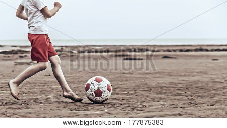 The child chases the ball at low tide on a deserted beach.