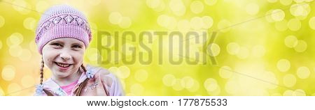 Cute little girl on a green background in a spring day. Free space for text.