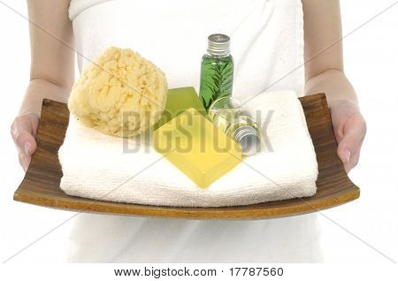 Woman holding a tray with lotion and washtub, white towels