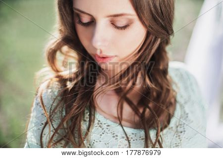 Beauty portrait of a very pretty young beautiful girl. Doll appearance. Beautiful woman with brown hair in a turquoise dress on nature. Long hair. Natural light. Beautiful model