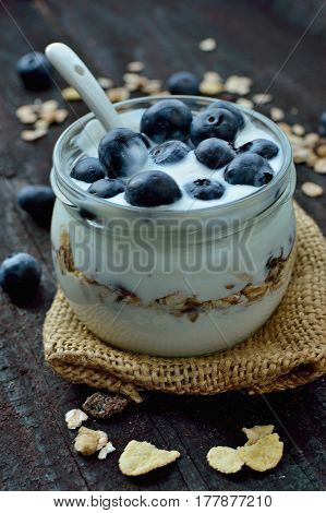 Fresh white yogurt with blueberries and oatmeals on brown wood table. Delicious natural breakfast. Culinary sweet dessert.