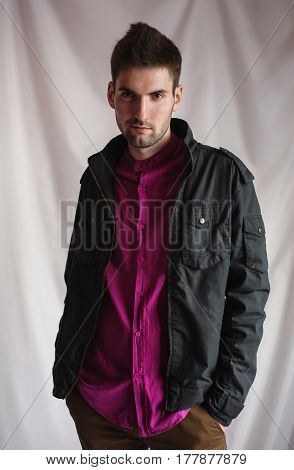 Young attractive cheerful brunette man with dark hair with a beard in a purple shirt and a black jacket on a white background. Men's style. Brunette male portrait. Studio photography