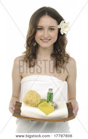 Attractive woman holding a tray with lotion and washtub, white towels