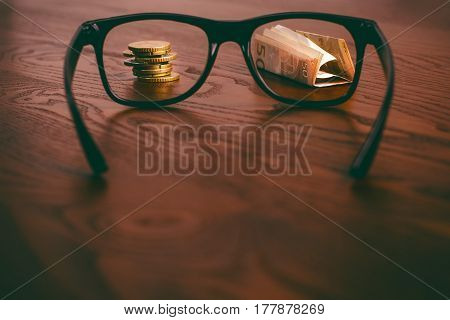 Euro money coins and paper money focused in glasses on a wooden table. Finance and office concept. Focused on money. Economy. Business background