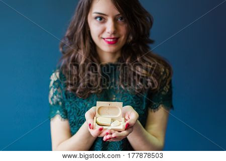 Young woman holding wooden usb stick and case for it in hands, closeup