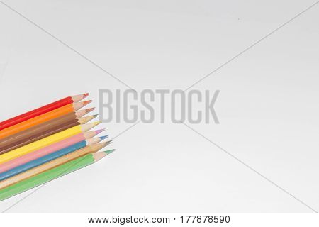 Blank paper and colorful pencils on the wooden table. View from above.