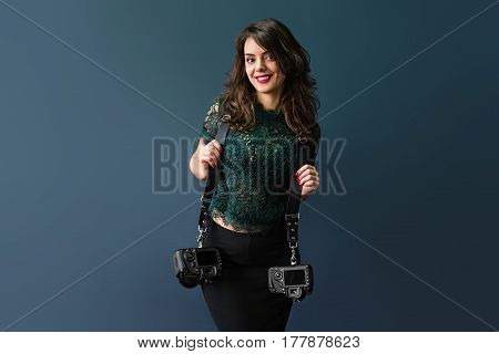 Woman holding two photographic cameras, isolated on a dark blue