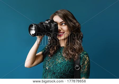 Woman takes images holding photographic camera, isolated on a dark blue