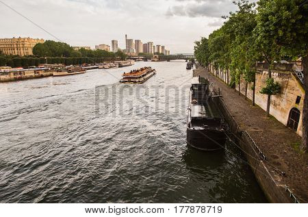 Walk on the ship on the river Seine in Paris. Travel Europe Landmarks in France. Grey Sky. The bridge over the river. Landscape with river