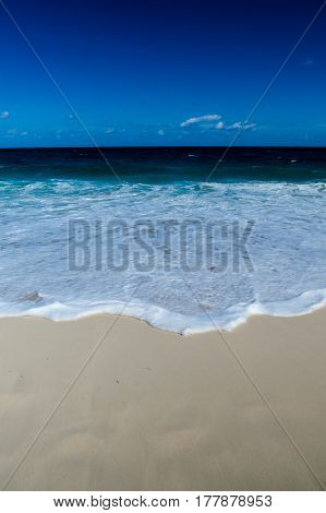A simple vertical photo of a tropical beach and the ocean. New Providence, Nassau, Bahamas.