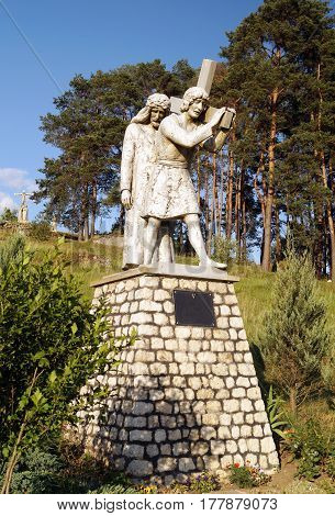 The Way of Jesus Christ: Simon helps to bear the cross of Jesus Christ on Calvary. (A statue on the Holy Mountain in the Ternopil region Ukraine)
