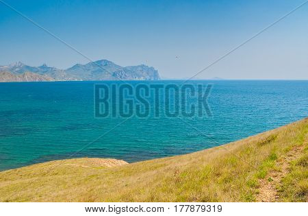 Landscape with view from Meganome cape to Kara-Dag volcanic mountain range on Crimean peninsula