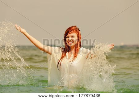 Summer fun recreation outside concept. Redhead adult woman playing in water during summertime having great time and smiling joyfully