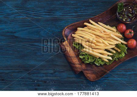 Fried potato on a blue wooden background