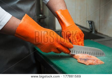 Chef cutting salmon fish on fillet with knife