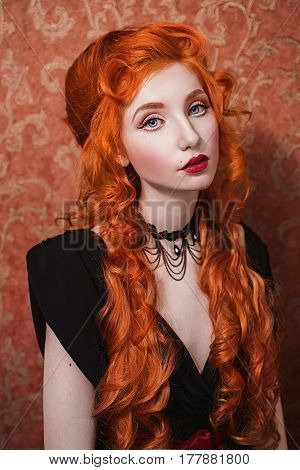 Red hair woman. Portrait of a woman with long red curly hair in a black and red dress and choker on her neck. Red-haired girl with pale skin blue eyes a bright unusual appearance and red lips. Long red hair