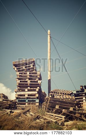 Wood pallets stacked with blue sky.
