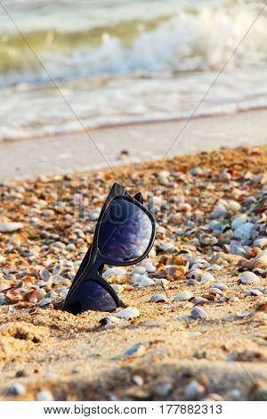Sunglasses with black frame on sumer sandy beach.