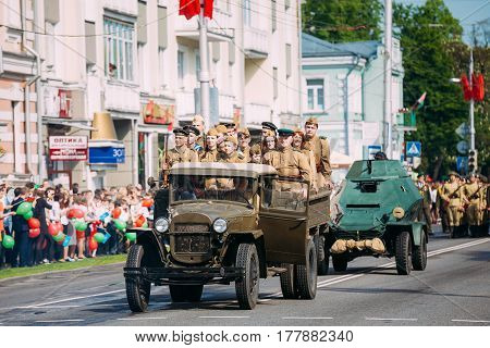 Gomel, Belarus - May 9, 2016: The Scene Of Victory Parade. Russian Soviet Military Truck ZIS-5V With Trailer Enginery Of WW2 Time And Armed People In Soldiers Uniform On Board Foreground.