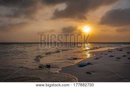 Sunset in the Maldives. Beautiful colorful sunset over the ocean in the Maldives seen from the beach.Amazing sunset and beach in Maldives. Calm water and soft waves. Beautiful maldivian sunbeam.