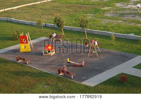 A small children`s playground with resting people