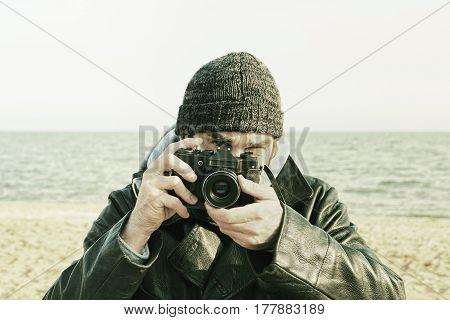 Photographer with retro photo camera on sea beach.Toned image.