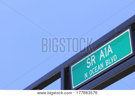 Outdoor green and white painted metal State Route A1A North Ocean Boulevard street sign. SR A1A N Ocean Blvd overhead on a public street sign post on a sunny blue sky day.