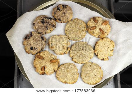 Blueberry almond and cinnamon cocoanut cookies on baking paper on two baking sheets. A few varieties of homemade coconut cookies on pans on a stovetop.