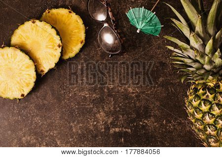 Summer fruit. Ripe pineapple and cocktail umbrellas leopard sunglasses on dark table with a marble texture with scratches. Cut summer fruit. Healthy eating. Going on a journey to the south. Flat lay top view. Copyspace. Summer concept