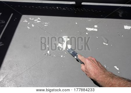 Male caucasian hand loosening flaky gray paint with a scraper outdoors on a sunny day. Adult hand of a man scraping worn gray paint from a small home cement deck.