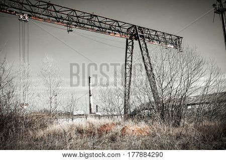 A broken old rusty crane. Abandoned ruins of the factory, factories.