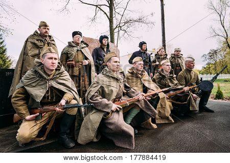 Pribor, Belarus - April 23, 2016: Re-enactors Dressed As Russian Soviet Infantry Soldiers Of World War II Standing  At Monument In Memory Of Fallen In Great Patriotic War