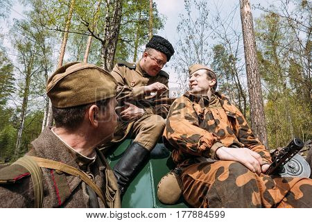 Pribor, Belarus - April 24, 2016: Re-enactor Dressed As Russian Soviet Red Army Soldiers Of World War II Sitting In Armoured Soviet Scout Car BA-64 In Forest.