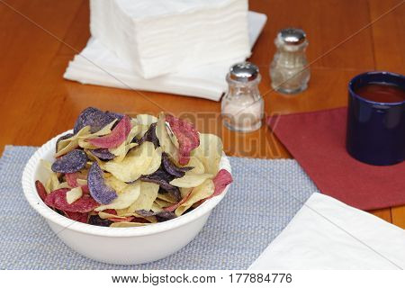 One bowl of red white and blue potato chips on a kitchen table with linens seasonings and beverage. Red white and blue potato chips in a bowl on a kitchen table.
