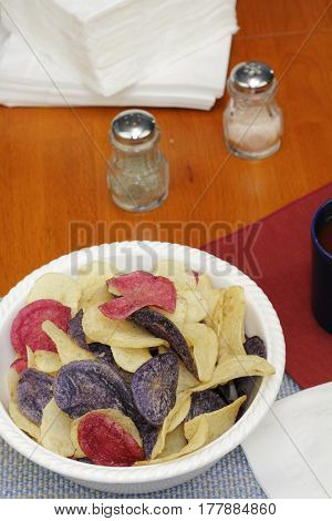 Bowl of three different colors of chips red yellow and purple usually referred to as red white and blue. Variety of potato chips in a white bowl on a table.