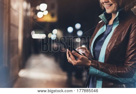 Girl smile pointing finger on screen smart phone on background illumination color light in night atmospheric city hipster using in female hands and text mobile phone mock up glitter street content lifestyle