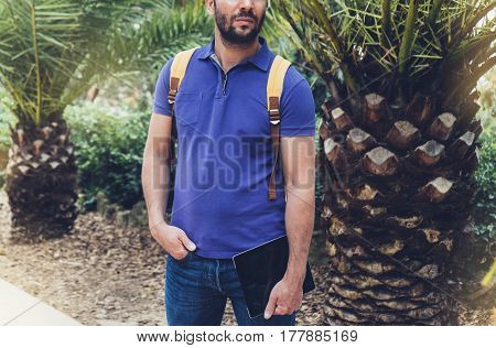 Hipster person holding in male hands digital tablet with blank screen front view guy standing in shirt with computer on background nature park palm landscape mock up technology blur tourist using gadget