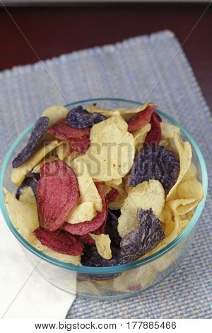 Red Crimson Purple Majesty Chipeta and Atlantic potato chips food. Close-up of red crimson purple blue and yellow white potato chips in a clear glass bowl.