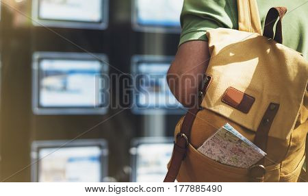 Hipster young man with backpack and map looking ad promo poster hotel choose apartments. Tourist traveler planning route on background advert hostel city. Person hiker select hotel backdrop summer street