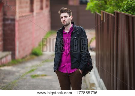 Young attractive cheerful man with dark hair with a beard wearing a shirt and a black jacket on the street. Male street style. Nature in spring. Attractive man walking around the city.
