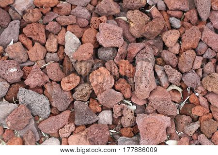 Many medium and small volcanic red rocks all together on the ground being used as ground cover. Red volcanic rocks ground cover background close-up outside in the day.