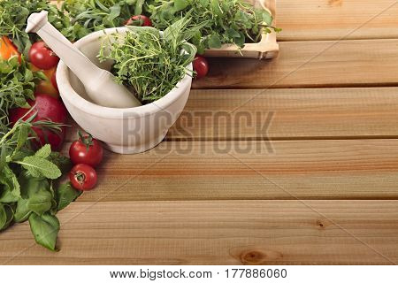Fresh herbs with a mortar and pestle and vegetables on a wooden worktop.