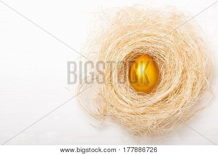 Golden egg in a nest on a white background. The concept of wealth luck business treasure prosperity.